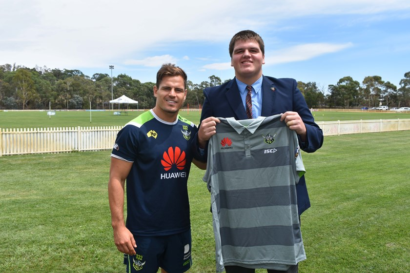 Aidan Sezer presents a Raiders Shirt for the upcoming Indigenous Youth Summit